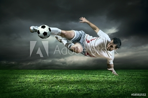 Picture of Football player with ball in action under rain outdoors