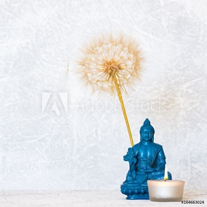 Picture of Buddha, burning candle and dandelion flower as zen background