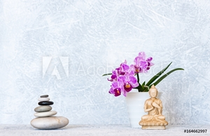 Picture of Buddha, pyramid of pebbles and orchid flower as zen background