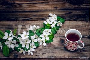 Picture of A branch of apple blossoms and a mug of tea on wooden background
