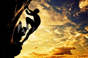 Picture of A silhouette of man climbing on mountain at sunset. Adrenaline