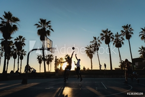 Picture of Friends playing basketball at sunset