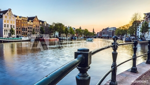 Picture of The most famous canals and embankments of Amsterdam city during sunset. General view of the cityscape and traditional Netherlands architecture.