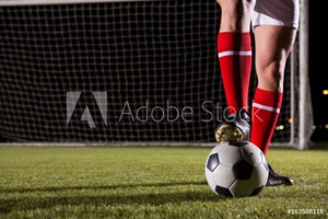Picture of Low section of male soccer player with ball on field
